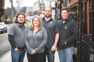 Prime Renovations team. Four people standing on city street. One woman and three men.